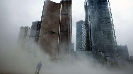 Un hombre camina cerca de unos rascacielos en construcción en Pekín, China.