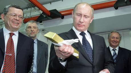 El presidente Vladímir Putin sostiene una barra de oro, en una visita el Depósito Central del Banco de Rusia.