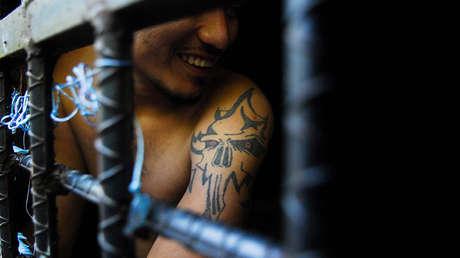 Un hombre arrestado por pertenecer a la pandilla Mara Salvatrucha, sonríe desde dentro de una celda de una cárcel en San Salvador el 12 de octubre de 2012.