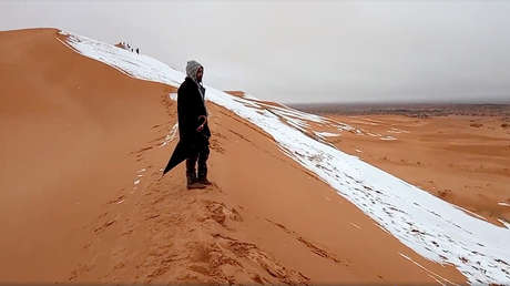 Un hombre observa una pendiente cubierta de nieve en el Sáhara, en el poblado de Aïn Séfra (Argelia), el 7 de enero de 2018.