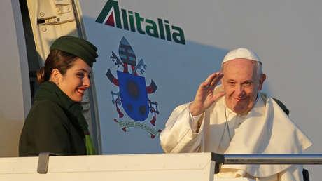 El papa Francisco saluda cuando aborda su viaje a Chile y Perú.