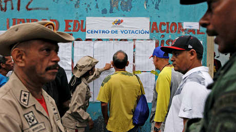 Personas revisan una lista durante una elección nacional para nuevos alcaldes. Caracas, 10 de diciembre de 2017.