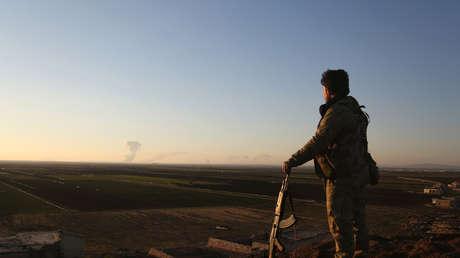 Un miliciano sirio observa desde el norte de Alepo las columnas de humo emanando de Afrín, el 20 de enero de 2018.