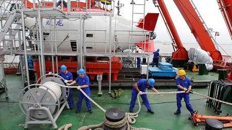 Personal trabaja en un barco frente al sumergible tripulado chino de inmersión profunda Jiaolong en Jiangyin, provincia de Jiangsu, el 1 de julio de 2011.