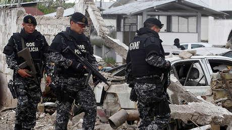 Policías caminan entre vehículos dañados tras la explosión en San Lorenzo (Ecuador), el 27 de enero de 2018.