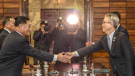 El jefe de la delegación surcoreana, Lee Woo Sung (a la derecha) saluda al jefe de la delegación del Norte, Kwon Hook Bong, durante una reunión en una aldea norcoreana, el 15 de enero de 2018.