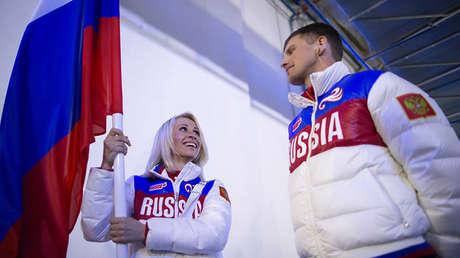 La esquiadora paralímpica rusa Mijalina Lýsova con la bandera nacional junto al atleta Alexéi Ivanov en la clausura de Sochi 2014