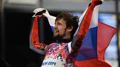 Alexánder Tretiakov pasea la bandera rusa al final de una competición de la disciplina de skeleton en los JJ.OO. de Sochi 2014.