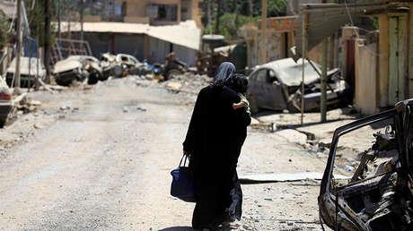 Una mujer desplazada camina con un niño en sus brazos, Mosul, Irak.
