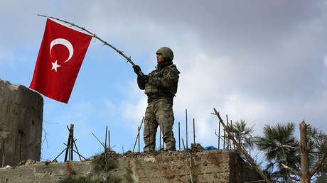 Un soldado turco agita una bandera en el monte Barsaya, al noreste de la ciudad siria de Afrín, el 28 de enero de 2018.