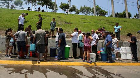 Los residentes recogen agua en una calle durante una escasez de agua después de que los ríos se salieron de sus orillas debido a las lluvias torrenciales, causando inundaciones y una destrucción generalizada en Lima, Perú, el 18 de marzo de 2017.