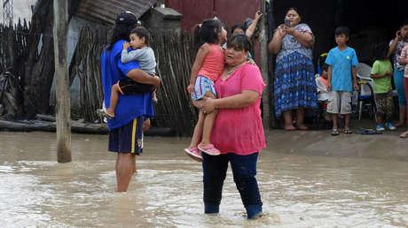 Ciudadanos levantan niños para cruzar una calle inundada en Salta, Argentina, en febrero del 2018.