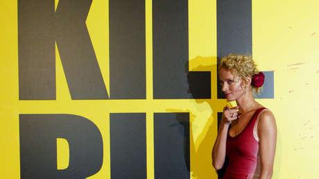"""La actriz Uma Thurman posa frente al póster de la película del director estadounidense Quentin Tarantino """"Kill Bill vol 1"""", el 4 de noviembre de 2003."""