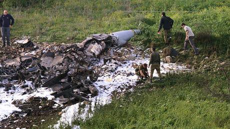 Miembros de las fuerzas de seguridad israelíes junto a los restos de un F-16 derribado, cerca de la aldea de Harduf (Israel), el 10 de febrero de 2018.