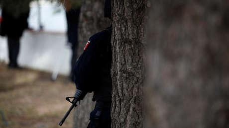 Un oficial de la Policía Federal vigila entre los árboles.