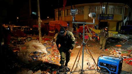 La policía inspecciona el sitio de la explosión de un tanque de gas durante el desfile de carnaval en Oruro.