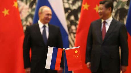 Banderas rusas y chinas se ven sobre la mesa con el presidente ruso Vladimir Putin y su homólogo chino Xi Jinping al fondo durante una ceremonia en Pekín, el 9 de noviembre de 2014.