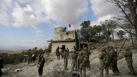 Un soldado del Ejército de Turquía ondea una bandera nacional en el monte Barsaya, al noreste de Afrín. Siria, 28 de enero de 2018.