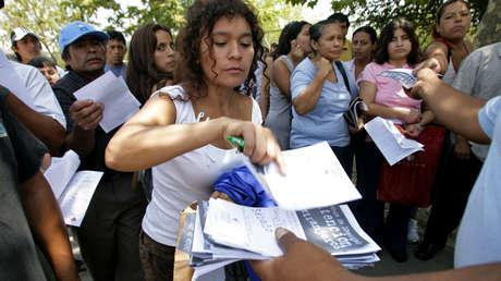 Inmigrantes rellenan formularios y hacen cola en el Estadio Nacional de Santiago de Chile, 5 de febrero de 2008