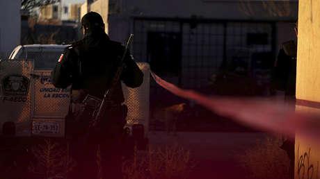 Un oficial de la policía vigila una escena del crimen donde atacantes  mataron a cuatro hombres en un garaje, en Ciudad Juárez, México, el 7 de febrero de 2018.