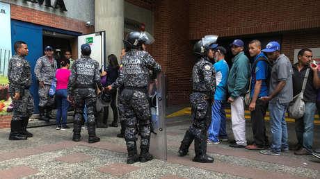 Policías custodian una fila de gente que compra azúcar a las afueras de un supermercado en Caracas.