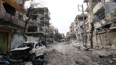 Vehículos y edificios dañados se ven en la ciudad sitiada de Duma, Guta Oriental,  Siria, el 25 de febrero de 2018.