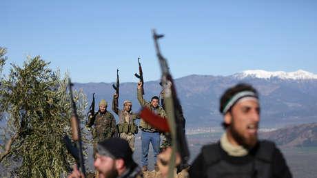 Los militantes del Ejército Libre Sirio apoyados por Turquía sostienen sus armas cerca de la ciudad de Afrín.