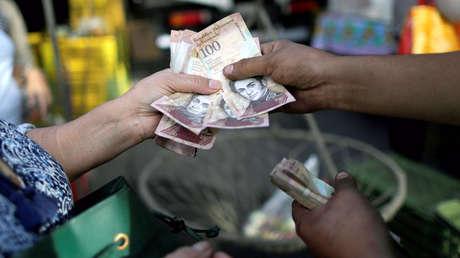 Un cajero recibe bolívares venezolanos de un cliente en un mercado en Caracas. Diciembre de 2016.