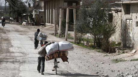 Los sirios empacan sus pertenencias mientras huyen de su hogar en la ciudad de Utaya en el enclave rebelde sirio de Guta Oriental el 1 de marzo de 2018.