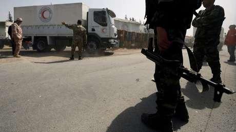Camiones con ayuda humanitaria atraviesan un control militar sirio.