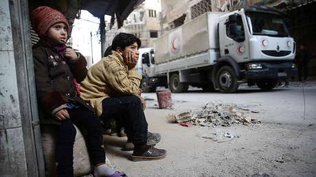 Niños miran como un convoy humanitario pasa por la ciudad de Duma, Guta Oriental, Siria, el 5 de marzo de 2018.
