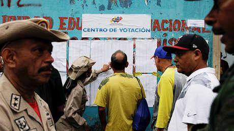 Personas revisan una lista de un centro de votación durante las elecciones en Caracas, el 10 de diciembre de 2017.