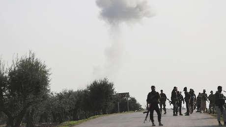 Una columna de humo se eleva mientras combatientes del Ejército Sirio Libre apoyado por Turquía avanza en el norte de Afrín, Siria, el 8 de marzo de 2018.