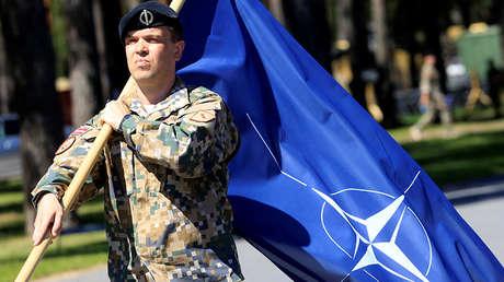 Un soldado letón porta la bandera de la OTAN en la ceremonia de bienvenida de un batallón de la Alianza en Adazi (Letonia), el 19 de junio de 2017.