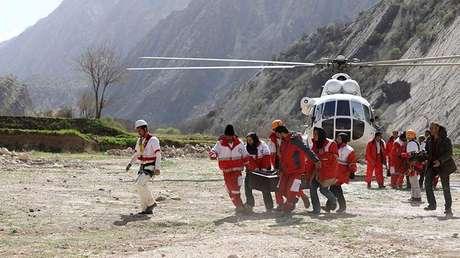 Los especialistas transportan el cuerpo de un pasajero tras el accidente aéreo ocurrido en los montes Zagros de Irán, el 12 de marzo de 2018.
