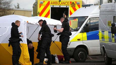 Los policías se ponen trajes de protección en un aparcamiento adonde fue transportado el vehículo de Serguéi Skripal en Salisbury, Reino Unido, el 13 de marzo de 2018.