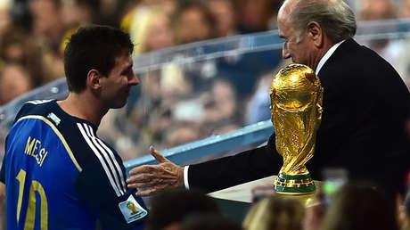El entonces presidente de la FIFA, Joseph Blatter, felicita a Lionel Messi tras concederle el Balón de Oro después del partido con Alemania, el 13 de julio de 2014 , Río de Janeiro.
