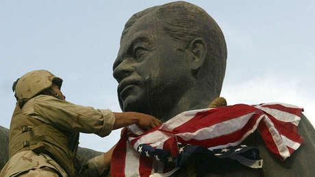 Un marine de EE.UU. cubre la cara de la estatua de Saddam Hussein con una bandera estadounidense, Bagdad, el 9 de abril de 2003.