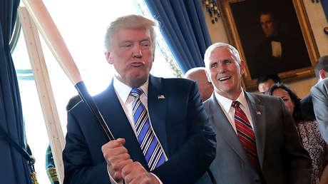 El vicepresidente de EE.UU., Mike Pence, ríe mientras el presidente Donald Trump sostiene un bate de béisbol en la Casa Blanca en Washington (EE.UU.), el 17 de julio de 2017.