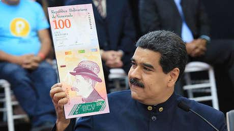 El presidente de Venezuela, Nicolás Maduro, con una imagen del diseño del nuevo billete de 100 bolívares, en Caracas, el 22 de marzo de 2018.