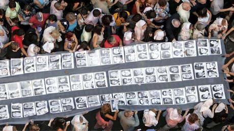 Manifestantes llevan una bandera con los rostros de los desaparecidos en Argentina, 24 de marzo de 2006.