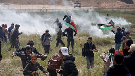 Palestinos huyen del gas lacrimógeno lanzado por las tropas israelíes durante los enfrentamientos en la frontera de Gaza, el 30 de marzo de 2018.