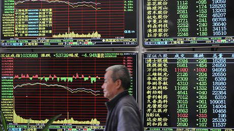 Un hombre pasa ante una pantalla electrónica que muestra información bursátil en Jiujiang (China), el 23 de marzo de 2018.