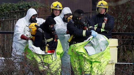 Agentes se quitan los trajes de protección cerca del lugar donde Serguéi Skripal y su hija Yulia fueron hallados inconscientes en Salisbury, en el sur de Inglaterra, el 8 de marzo de 2018.