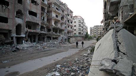 Residentes de Duma pasan junto a edificios destruidos, el 24 de noviembre de 2013.