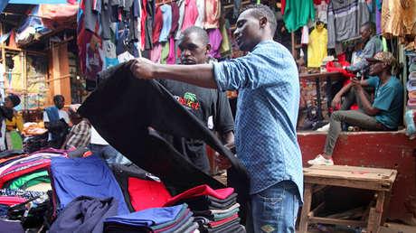 Dos hombres miran unos pantalones de segunda mano en un mercado, Kampala, Uganda, 6 de abril de 2018.