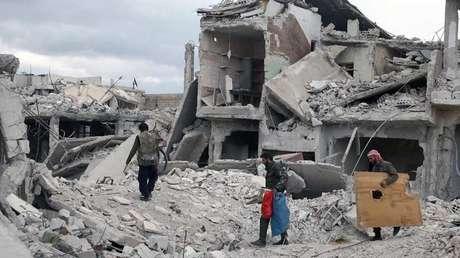 Unos hombres caminan sobre los escombros de edificios dañados en la ciudad sitiada de Duma, Guta Oriental, en Siria, el 30 de marzo de 2018.