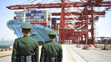 Agentes de la Policía frente a un buque de carga en el puerto chino de Qingdao, el 6 de abril de 2018.