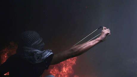 Un manifestante palestino lanza piedras contra las fuerzas de Israel, frontera de la Franja de Gaza, 20 de abril de 2018.