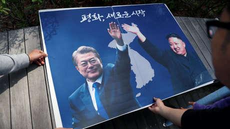 Cartel con las imágenes de los líderes de las dos Coreas durante el encuentro entre ambas naciones en Seúl, Corea del Sur, el 26 de abril de 2018.